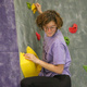 This is a photo of a girl with red hair and glasses on the rock wall. She is looking down and pickling up her left leg. She wears a purple tshirt and black leggings. Her left hand is resting on a yellow hold, and her right hand is reaching above her head to keep hold of a yellow grip in the background of the picture.