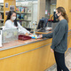 A young woman wearing a mask is returning a book at the Library circulation desk.
