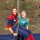 This is a photo of a girl dressed up as a doctor holding a guy dressed in a Spiderman onesie. The guy is sitting in a harness and is being held mainly by the rope. The rock wall is behind both of them.
