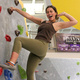 This is a photo of a girl climbing. She is towards the top of the wall and leaning back with one hand holding onto a grip and the other behind her head as she poses and smiles.