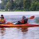 This is a photo of a lady with a head scarf paddling in a kayak next to a man with a ball cap and glasses in his kayak. She holds the paddle up as if she is about to put the right paddle in the water. She is smiling, and her profile is visible to the camera. They are on the water, and there is a lush green tree line in the background of the photo.
