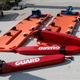 """A photo of lifeguard gear on the ground. There are three red life guard floats that state """"guard"""" in white block letters next to orange stretchers that float in the pool."""