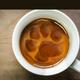 A white coffee mug with coffee inside showing a Huskie paw print.