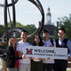 Staff and students hold a sign 'Welcome International Students' near the sundial