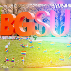 Large BGSU letters outside of the Union with gay pride rainbow flags in the lawn around the letters.