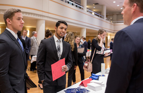 Students talk with an employer at a career fair