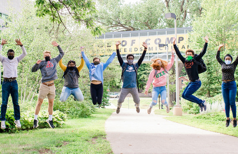 Students in masks jumping in unison in front of the Michigan Tech Library.