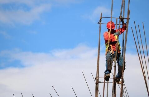 construction worker in orange vest and hard hat climbing  up a structure