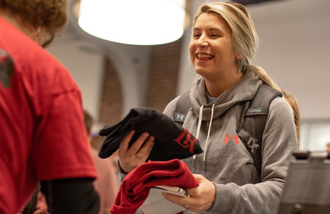 A student smiles while being handed t-shirts.