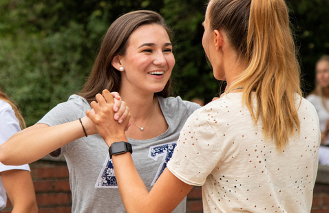 Two students face each other and embrace hands.