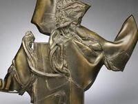color photograph of a brass/bronze sculpture with a white shadowy background