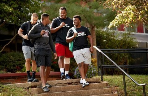 Group of students talk as they walk down stairs on campus