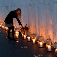 A woman places flowers at the 9/11 memorial. Lit candles are shown to line the wall of the memorial.