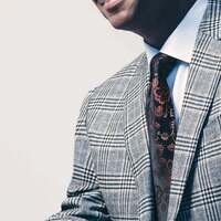 Photo of renowned saxophonist Branford Marsalis sitting down wearing a blazer