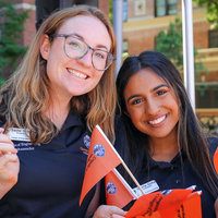 Two women students smiling while holding College of Engineering orange flags
