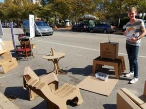 photo of young man surrounded by cardboard furniture standing in a parking space