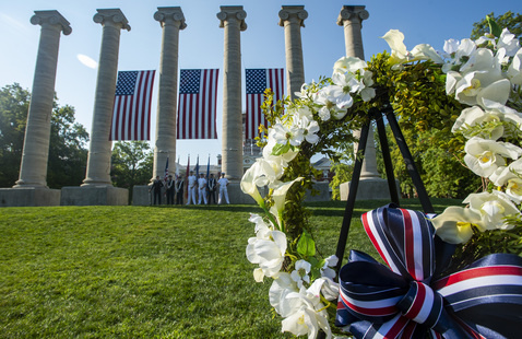 Wreath with columns, Joint Colorguard, and American flags in the background.