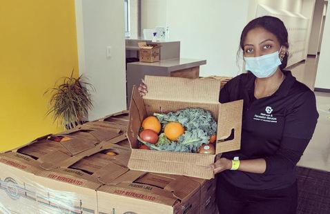 Student with Farm Fresh Produce box