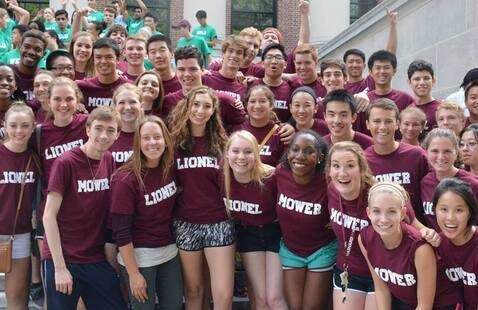 Students in dorm t-shirts gathered together on library steps. smiling