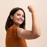Woman flexing with bandage on arm.