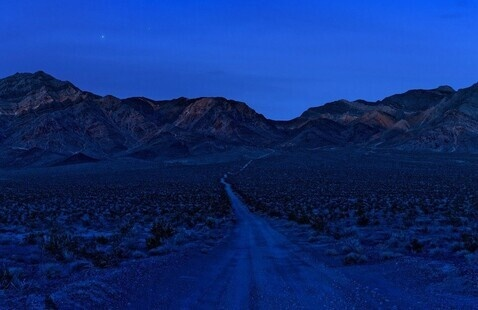 A photograph of a road leading into mountain range.