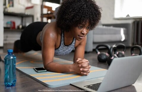 Woman exercising in front of a laptop