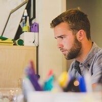 a young white man focuses on work at a desk