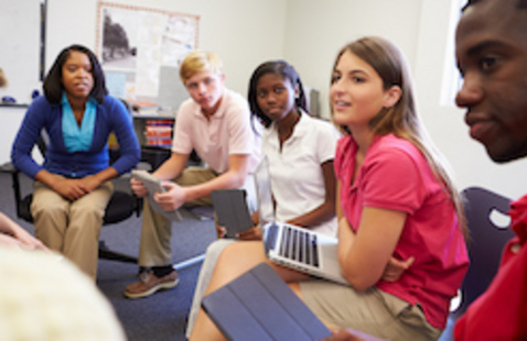 Group of students in a classroom listening to someone talk.