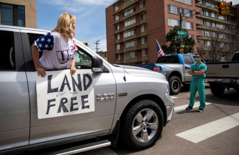 Medical professional standing in front of car with woman outside of window holding a Land of the free sign.