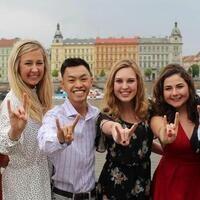 4 students in Europe signing Hook 'em Horns