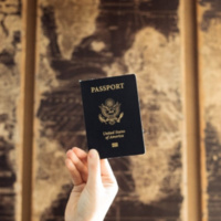 United States' Passport held in front of a world map.