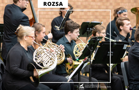 Three french horns play in the Superior Wind Symphony in front of a brick wall