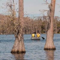Two people in yellow lifejackets canoe on Lake Bradford