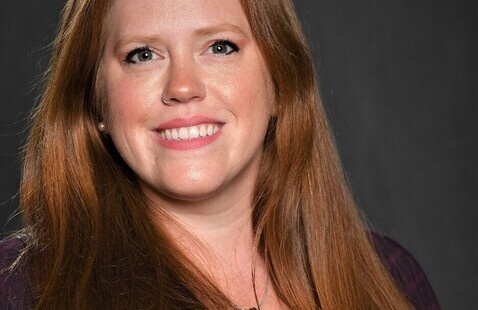 A photo of Teresa Halbert. She is a white woman with long red hair, brown eyes, black top, and a necklace. She is smiling in a professional photo.