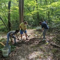 Three people with hand tools work on a trail