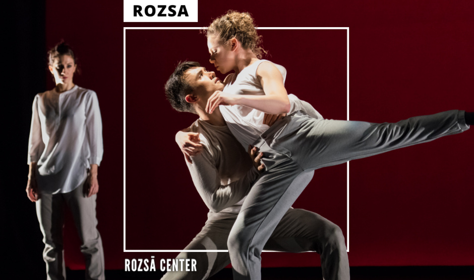 Two dancers embrace elegantly while another dancer looks on