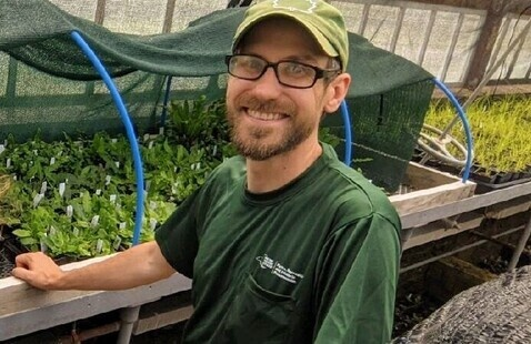 Speaker Mike Serviss standing by a greenhouse bench with young ferns