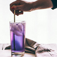 Hand holding straw that is in purple drink