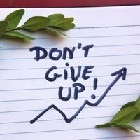 """""""Don't Give Up!"""" written on lined paper"""