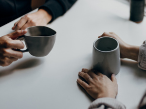 Close up of two people with coffee at table