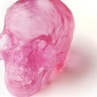 Photo of a pink, glass human skull.