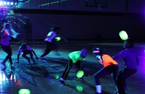 Students playing black light dodge ball in a gymnasium