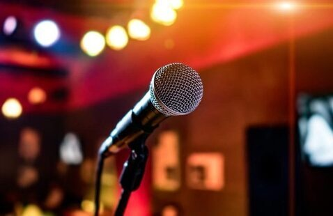 Lone karaoke microphone on lighted stage
