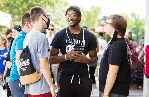Four students talking outside during new student orientation
