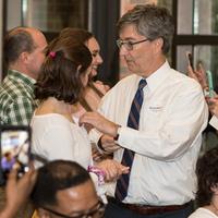 Alumnus pinning legacy pin on daughter