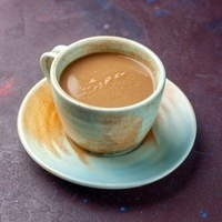 A latte in a mug with a saucer on a table