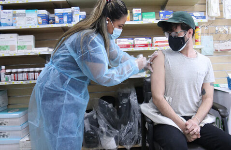 healthcare worker in mask and gown giving a vaccine to a patient in a mask