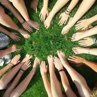 A circle of hands and feet on green grass