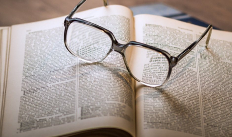 Glasses sitting on top of an open book