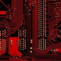 Red and gold circuits on a black circuit board - credit michael dziedzic on unsplash